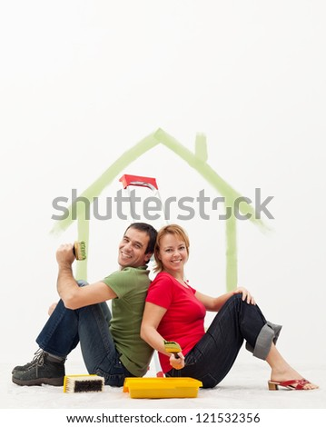Young couple in their new home with painting utensils - stock photo