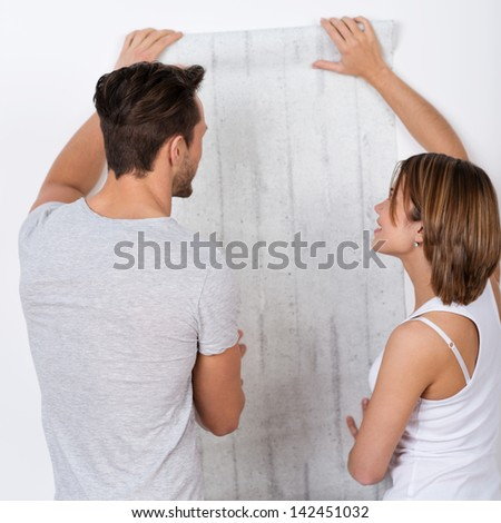 Young couple is choosing a new wallpaper - stock photo