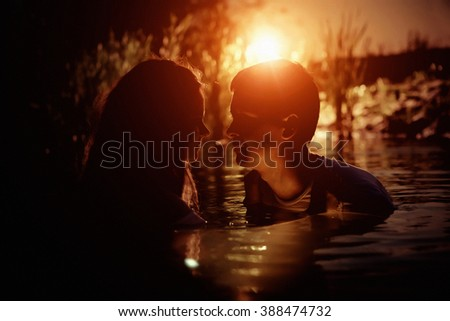 Young couple is kissing in the river on the summer sunset background. Sun flares are the part of composition. - stock photo
