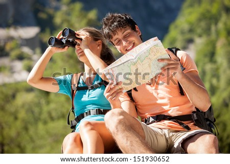 Young couple is looking at the map while sitting on a rock - stock photo