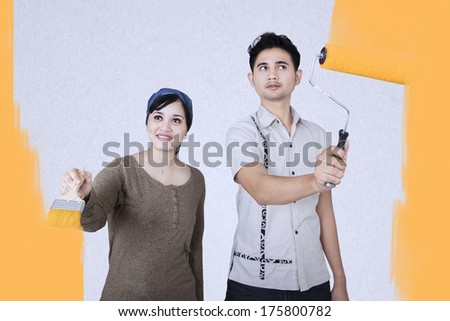 Young couple is painting in yellow color the wall of their new home - stock photo