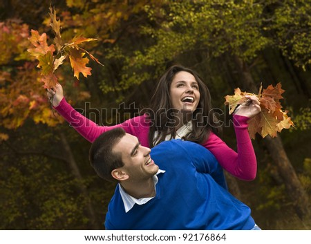 Young couple is playing piggyback in the autumn park - stock photo