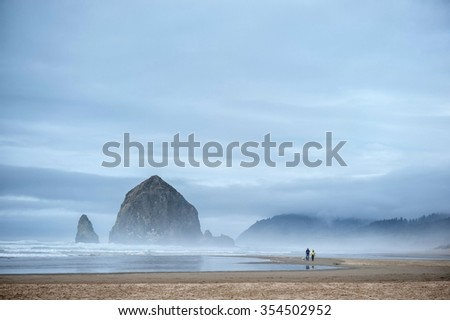 Young couple is walking with dog along Cannon Beach near Haystack Rock in Pacific Ocean - stock photo