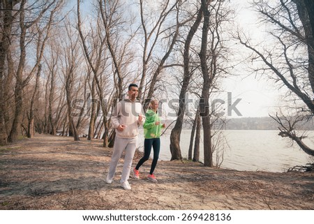 Young couple jogging in a park by the river - stock photo