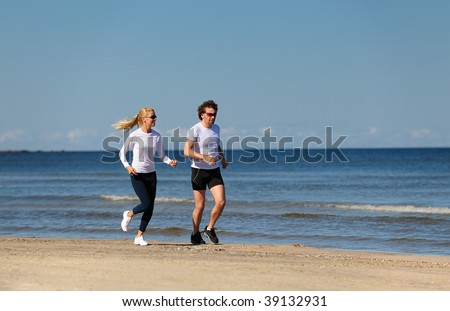 Young couple jogging on the beach - stock photo