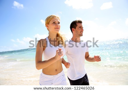 Young couple jogging on the beach in morning time - stock photo