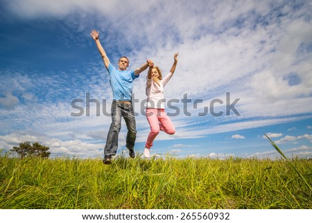 Young couple jumping on background of blue sky.
