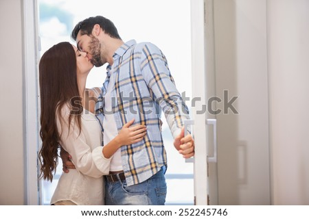 Young couple kiss as they open front door in their new home - stock photo