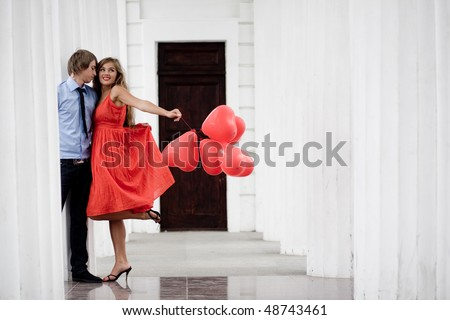 Young couple kissing among white columns and holding bunch of baloons-hearts - stock photo