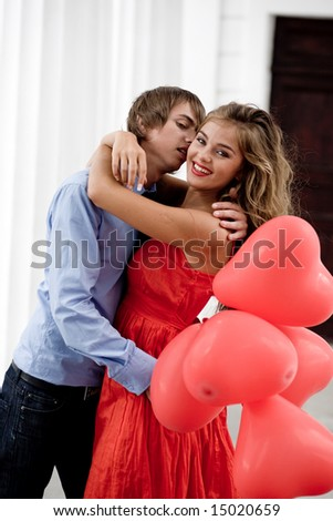 Young couple kissing and embracing among white columns and holding bunch of balloons-hearts - stock photo