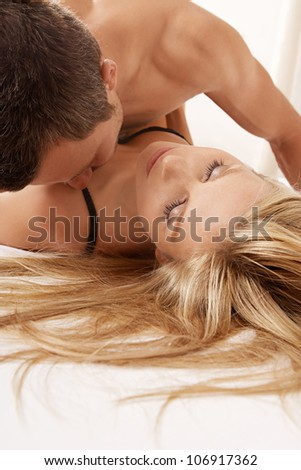 Young couple kissing and hugging in bed. - stock photo