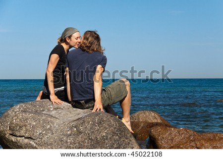 young couple kissing at the beach - stock photo