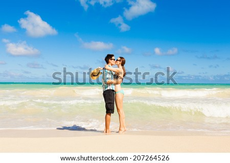 Young couple kissing at the beach in Hawaii. - stock photo