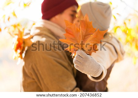 young couple kissing behind big leaves in autumn - stock photo
