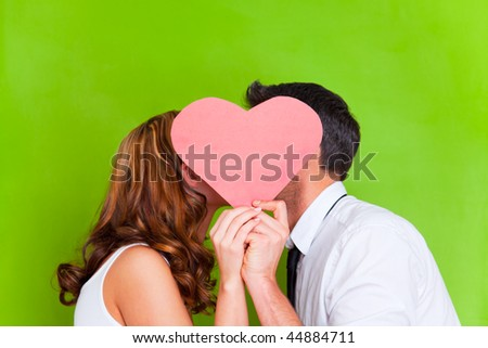 Young couple kissing behind pralines heart on valentines day