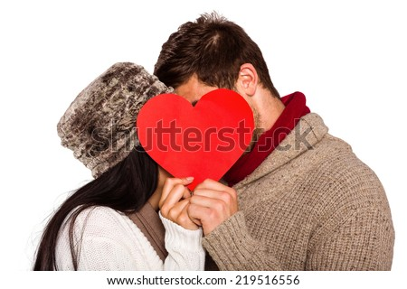 Young couple kissing behind red heart on white background