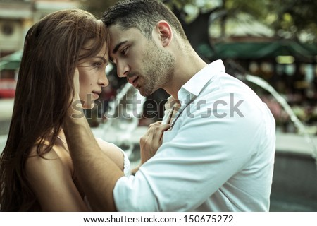 Young couple kissing each other on the street - stock photo