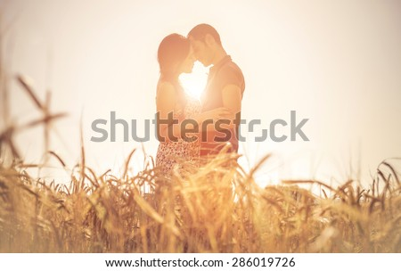 young couple kissing in a field. asian woman hugging a caucasian man in the middle of a wheat field and kissing each other. concept about passion and love - stock photo
