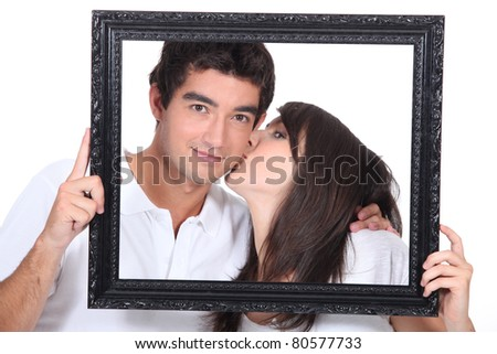 Young couple kissing in a frame - stock photo