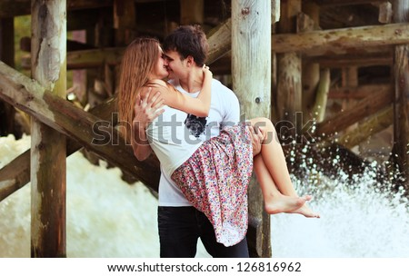 Young couple kissing in summer near waterfall. - stock photo