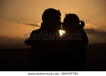 young couple kissing in sunset - stock photo