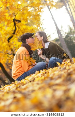Young couple kissing in the park while hiding the kiss with leaf. - stock photo