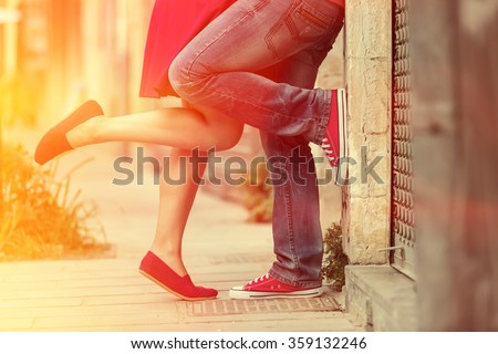 Young couple kissing outdoor. Male and female legs. Cross processed image for vintage look - stock photo