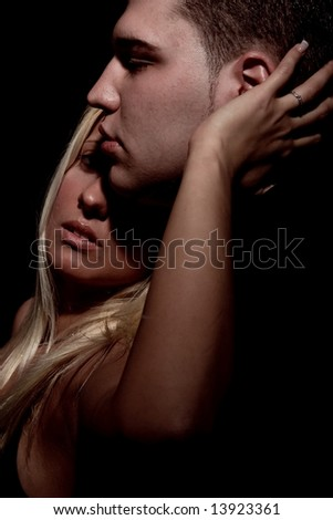 young couple kissing, studio shot in dark - stock photo