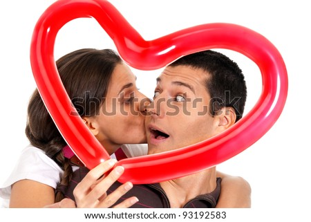 Young couple kissing through balloon heart surprise isolated on white background - stock photo