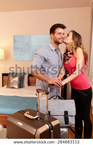 Young couple kissing upon arrival to hotel room. - stock photo