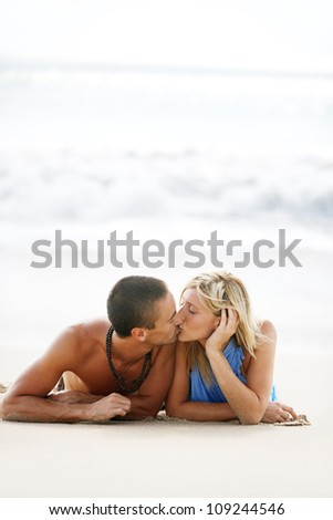 Young couple kissing while laying down on a golden sand beach shore on vacations. - stock photo