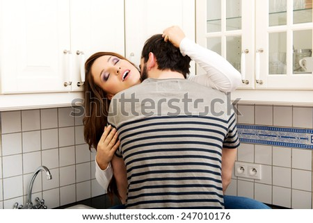 Young couple kissing with desire in the kitchen. - stock photo
