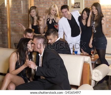 young couple kissing with friends behind laughing in moving focus on the couple - stock photo