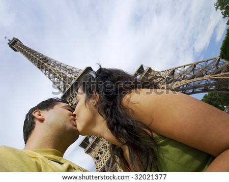 Young couple kissing with the magnificient Eiffel Tower at the background - stock photo