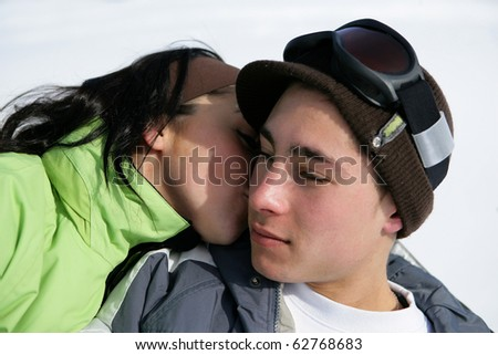Young couple laid in snow - stock photo