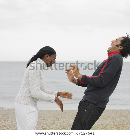 Young couple laughing and playing on beach - stock photo