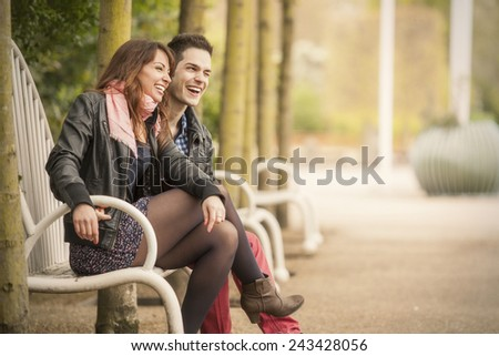 young couple laughing on bench in spring park - stock photo