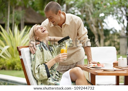 Young couple laughing while having a luxury breakfast in a tropical garden while on vacations. - stock photo