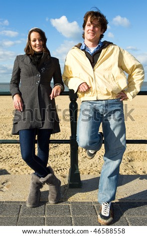 Young couple leaning against a fence on the beach on a beautiful autumn afternoon - stock photo