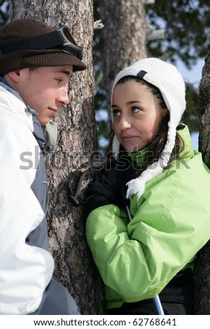 Young couple leaning on a tree - stock photo