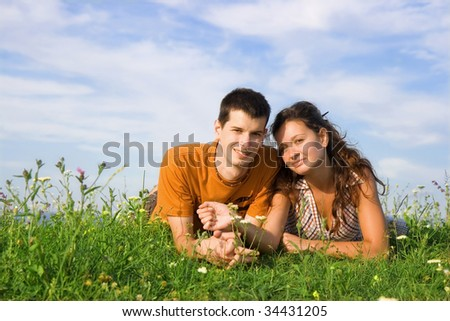 Young couple lie on the grass - stock photo