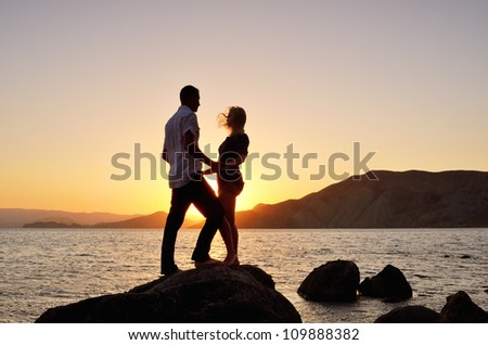 Young couple looking at each other, holding hands on beach - stock photo