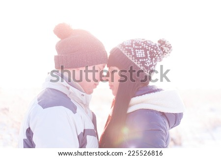 Young couple looking at each other in winter - stock photo