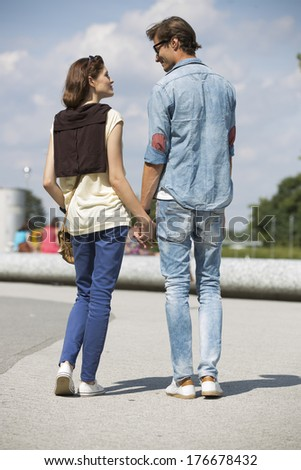 Young couple looking at each other while holding hands on street - stock photo