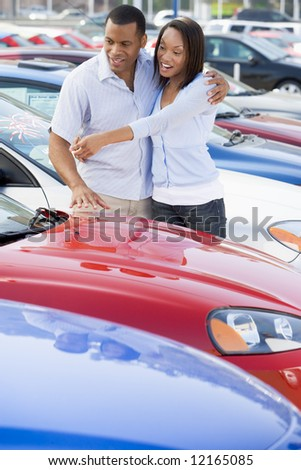 Young couple looking at new cars on lot - stock photo