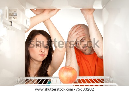 Young couple looking at ripe apple in otherwise empty refrigerator.