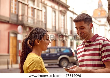 Young couple looking at the cell phone smiling happily while facing each other dressed casually t-shirts with buildings behind them - stock photo