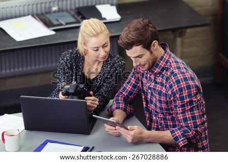 Young Couple Looking at the Tablet Screen Together While Sitting at the Table with Laptop Computer - stock photo