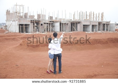 Young couple looking at their new investment, still under construction - stock photo