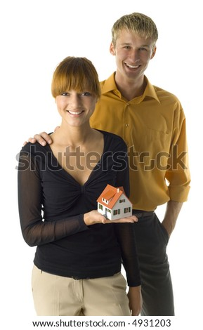 Young couple looking happy. Woman is holding house miniature. They're looking at camera. Front view, white background - stock photo